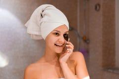 Kobieta w łazience stosuje podbite oko łaty Skóry opieka i zdroju ranku pojęcie zdjęcie stock