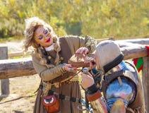 Kobieta w średniowiecznych ubraniach daje pić rycerza Obrazy Royalty Free