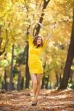 Kobieta w żółtej sukni z jesień liśćmi w ręce i spadku żółty klon uprawiamy ogródek tło Zdjęcia Royalty Free