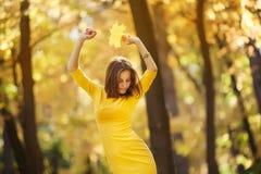 Kobieta w żółtej sukni z jesień liśćmi w ręce i spadku żółty klon uprawiamy ogródek tło Fotografia Royalty Free