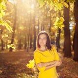 Kobieta w żółtej sukni z jesień liśćmi w ręce i spadku żółty klon uprawiamy ogródek tło Obraz Stock