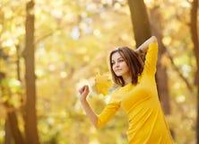 Kobieta w żółtej sukni z jesień liśćmi w ręce i spadku żółty klon uprawiamy ogródek tło Obraz Royalty Free