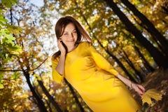 Kobieta w żółtej sukni z jesień liśćmi w ręce i spadku żółty klon uprawiamy ogródek tło Fotografia Stock