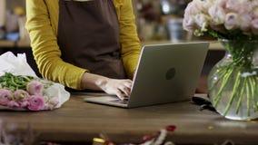 Kobieta w żółtych bluzka drukach pości na laptopie, w górę planu na ona ręki zbiory wideo