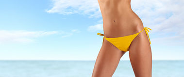 Kobieta w żółtym bikini na morza i nieba tle Obrazy Stock