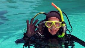 Kobieta w akwalungu pikowaniu robi ok znakowi zbiory
