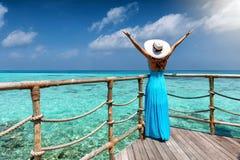 Kobieta w błękit sukni cieszy się widok tropikalny, turkusowy ocean, Zdjęcia Royalty Free