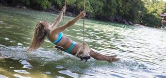 Kobieta w błękitnym bikini na linowych huśtawkach Fotografia Royalty Free