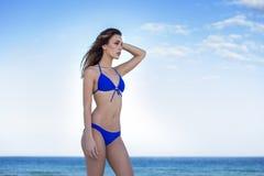 Kobieta w błękitnym bikini przy plażą, patrząc z Obraz Stock