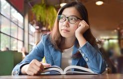 Kobieta w Błękitnym koszulowym główkowaniu podczas gdy czytający książkę Obraz Stock
