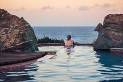 Kobieta w basenie przegapia morze obraz stock
