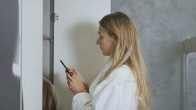 Kobieta w bathrobe bierze telefon od spiżarni w przebieralni zbiory wideo