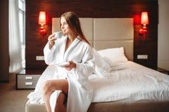 Kobieta w bathrobe chwytach wewnątrz wręcza filiżankę kawy zdjęcia royalty free