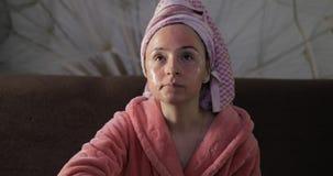 Kobieta w bathrobe z twarzow? mask? Ogl?da? nocnego film przy TV zdjęcie stock