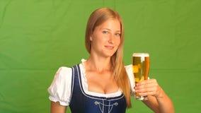 Kobieta w bavarian kostiumu śmia się aprobaty i pokazuje zielony ekran zbiory