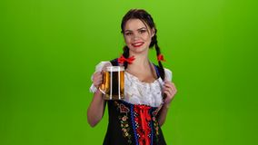 Kobieta w Bawarskim kostiumu tanczy z szkłem piwo w pickup zielony ekran zbiory