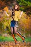 Kobieta w beżowym pulowerze i czarna skóry spódnica skaczemy Zdjęcia Stock