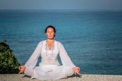 Kobieta w białej ćwiczy lotos pozie morzem Zdjęcia Stock