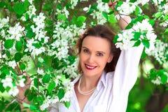 Kobieta w białej koszula pozuje w kwiatonośnych jabłoniach obraz royalty free
