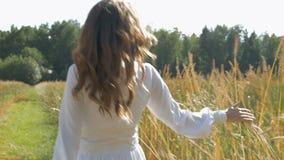 Kobieta w białej sukni chodzi wzdłuż pola z banatką swobodny ruch zdjęcie wideo