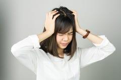 Kobieta w białej sukni dotyka głowę pokazywać jej migrenę Przyczyny mogą powodować stresem lub migreną obrazy stock