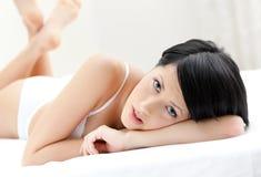 Kobieta w biały bieliźnie jest kłama w łóżku Zdjęcia Royalty Free