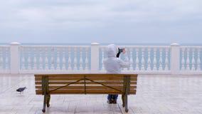 Kobieta w białym kapiszonie i kurtce strzela denne fale wideo na smartphone obsiadaniu na ławce na pięknym tarasie z morzem zbiory wideo