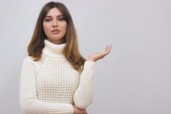 Kobieta w białym pulowerze pokazuje coś z otwartą ręki palmą Zdjęcia Stock