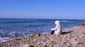 Kobieta w białym puszka kapiszonie i kurtce siedzi na brzeg i spojrzenia przy burzowym morzem machają bicie przeciw kamieniowi zdjęcie wideo