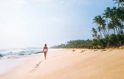 Kobieta w białym swimsuit chodzi na osamotnionego piaska tropikalnej plaży Obraz Stock