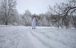 Kobieta w białym tracksuit bieg na nartach na śladzie kłaść w drewnach fotografia royalty free