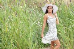 kobieta w białej sukni na tle wysoka trawa Zdjęcia Royalty Free