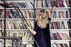 Kobieta w bibliotecznym bierze książkę od półka na książki Obrazy Royalty Free