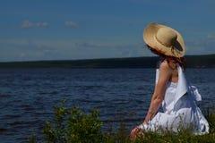 Kobieta w biel sukni i kapelusz relaksujemy na brzeg rzeki Obraz Royalty Free