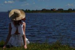Kobieta w biel sukni siedzi na brzeg rzeki, tylny widok Zdjęcie Stock