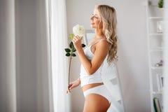 Kobieta w bieliźnie z róża kwiatem przy okno fotografia royalty free