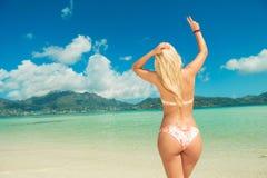 Kobieta w bikini pokazuje zwycięstwo znaka podczas gdy patrzejący w odległość fotografia royalty free