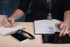 Kobieta w biznesów ubraniach pisze w notatniku, Fotografia Royalty Free