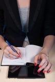 Kobieta w biznesów ubraniach pisze w notatniku, Fotografia Stock