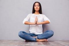 Kobieta w cajgach medytuje na podłoga Fotografia Royalty Free