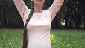 Kobieta w ciąży ćwiczy joga w parku, siedzący w lotosowej pozycji, trzymający ręki nad medytować i zbiory wideo