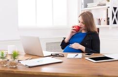 Kobieta w ciąży łasowania jabłko w biurowej kopii przestrzeni Zdjęcia Stock