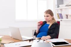 Kobieta w ciąży łasowania jabłko w biurowej kopii przestrzeni Obraz Royalty Free