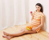 Kobieta w ciąży łasowania owoc Obrazy Stock