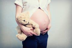 Kobieta w ciąży brzuch z misiem pluszowym Obraz Royalty Free
