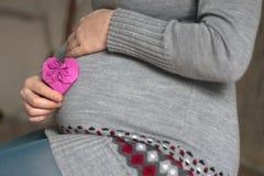 Kobieta w ciąży chwyta kierowy symbol przy jej brzuszkiem Obrazy Stock