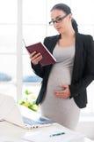 Kobieta w ciąży czytelnicza książka. obraz stock