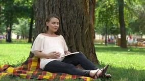 Kobieta w ciąży czytelnicza książka w parku, zdrowie i prenatal opiece, relaksuje outdoors, zbiory wideo