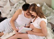Kobieta w ciąży i jej mąż pisze ciążowym dzienniczku. obraz royalty free