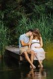 Kobieta w ciąży i jej męża obsiadanie przy jeziorem podczas gdy całuje jej ramię delikatnie zdjęcie royalty free